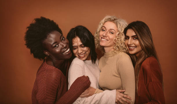 Group of cheerful young women standing together Group of cheerful young women standing together on brown background. Multi ethnic female friends in studio. four people stock pictures, royalty-free photos & images