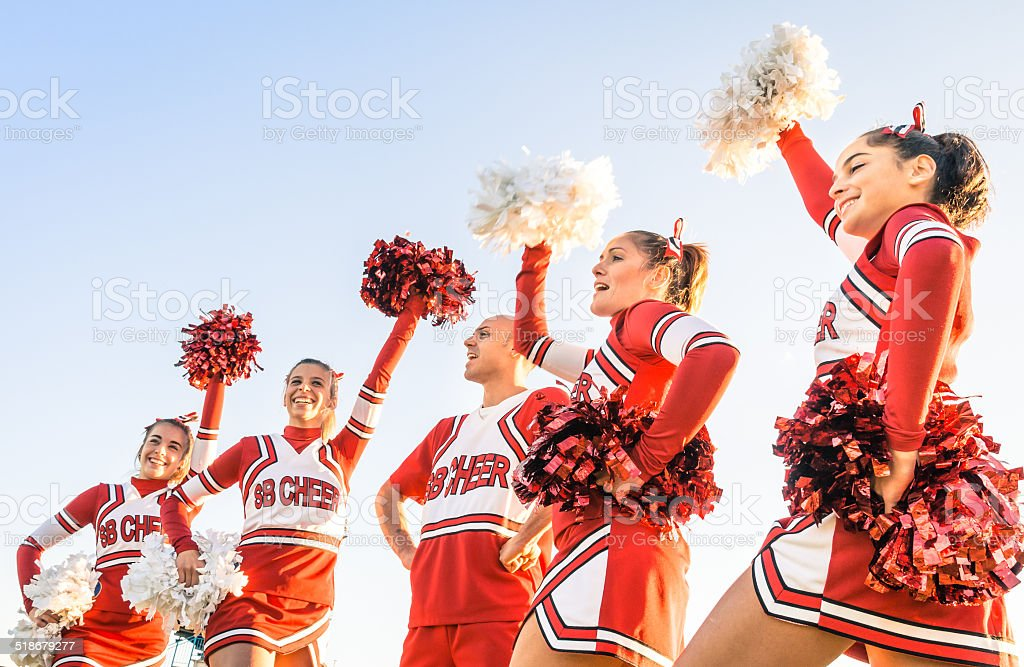 Group of cheerleaders in action with male coach stock photo