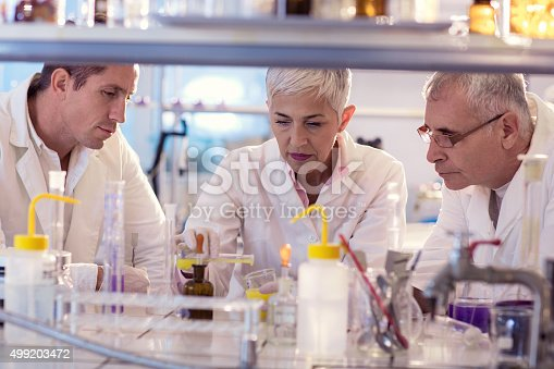 499203366istockphoto Group of chemists working on a new scientific experiment. 499203472