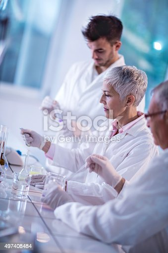 499203366istockphoto Group of chemists working on a research in laboratory. 497408484