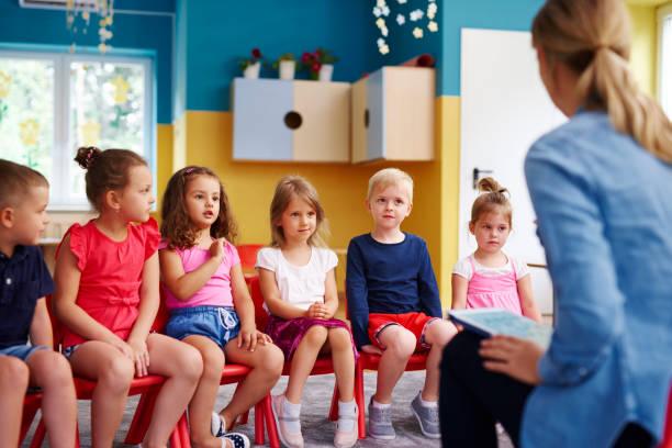 Group of children and teacher  in the preschool stock photo