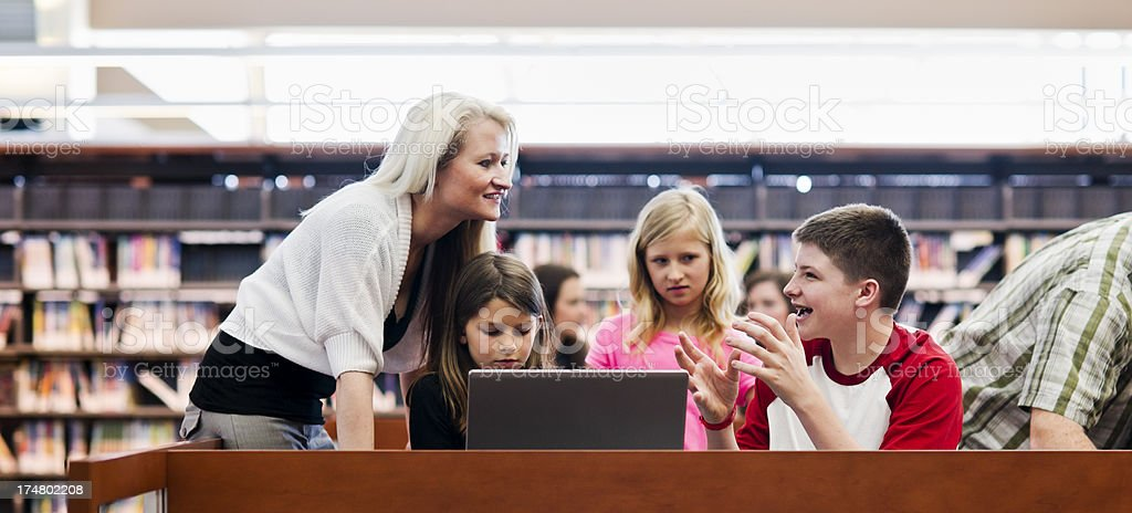 Group of children around laptop talking to adult in library royalty-free stock photo