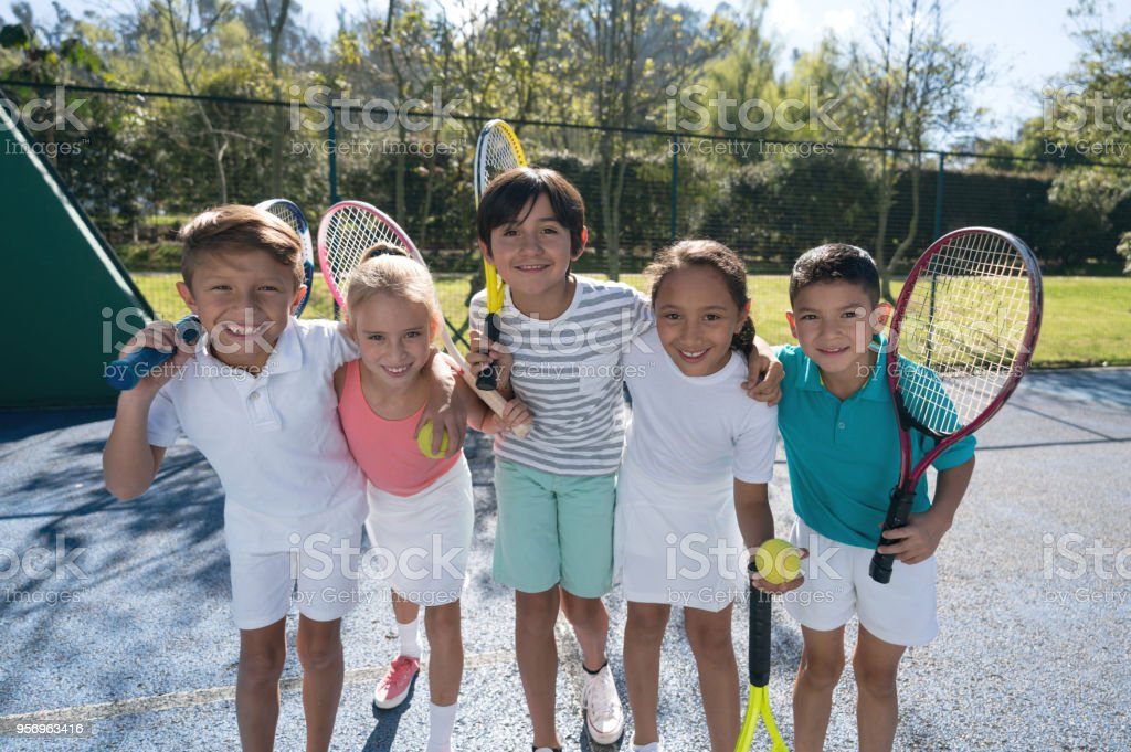 Groupe d'enfants à la Cour de tennis embrassant mutuellement et tenir leurs raquettes regardant sourire caméra - Photo