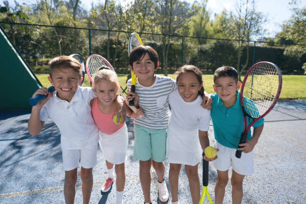 group of children at the tennis court embracing each other and holding their rackets looking at camera smiling - racket sport stock pictures, royalty-free photos & images