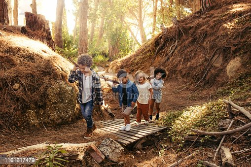 Group of children building camp in forest together. Boys and girls carrying sticks and walking
