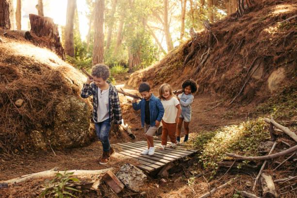 groep van kinderen bouw kamp in bos - bos spelen stockfoto's en -beelden