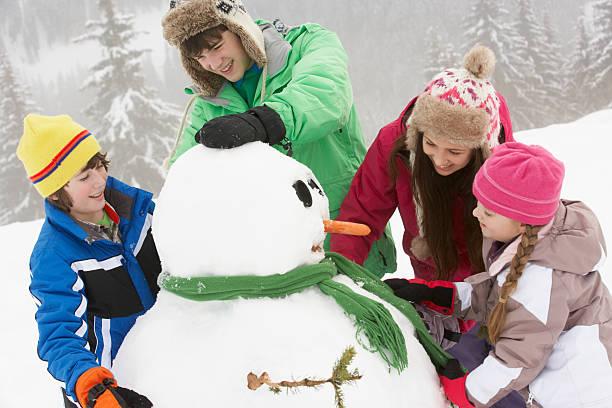 gruppe von kindern gebäude schneemann auf ski-urlaub in den bergen - schneemann bauen stock-fotos und bilder