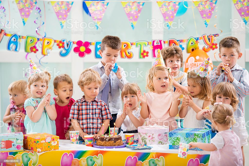Group of children celebrating and singing at birthday party. stock photo