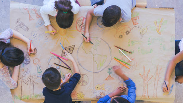 Group of children color environmentally conscious mural Aerial overhead view of a multi-ethnic group of elementary age children drawing. They are seated around a table. The kids are using colored pencils to make a mural. The have colored a world map, objects found in nature, and symbols of environmental conservation. global village stock pictures, royalty-free photos & images
