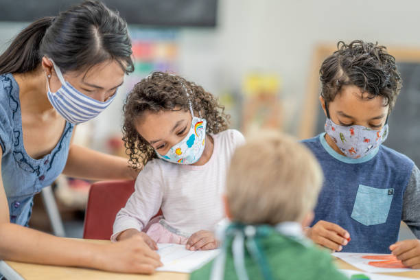 Group of children colouring while wearing masks stock photo