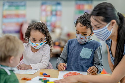Multi-ethnic group of children colouring at a table while wearing protective face masks to avoid the transfer of germs.