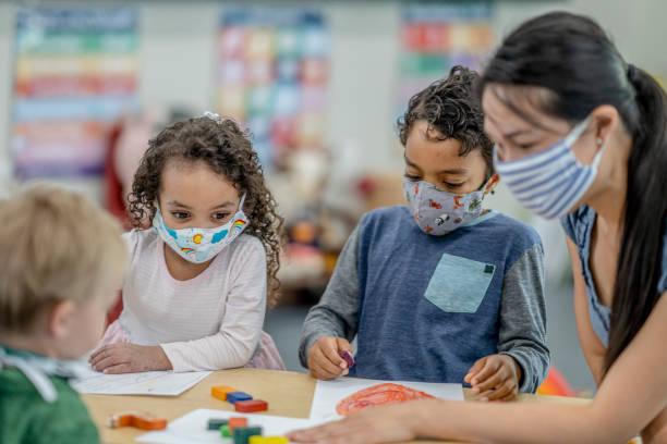 groupe d'enfants colorant tout en portant des masques - masque enfant photos et images de collection