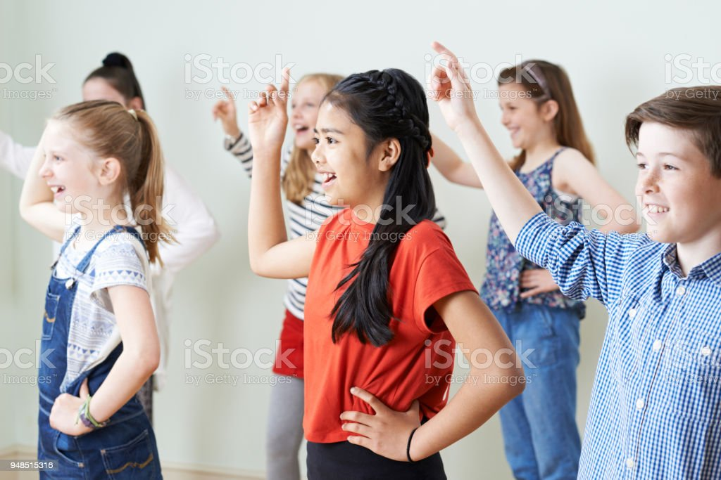 Group Of Children Dancing In Drama Class Together stock photo