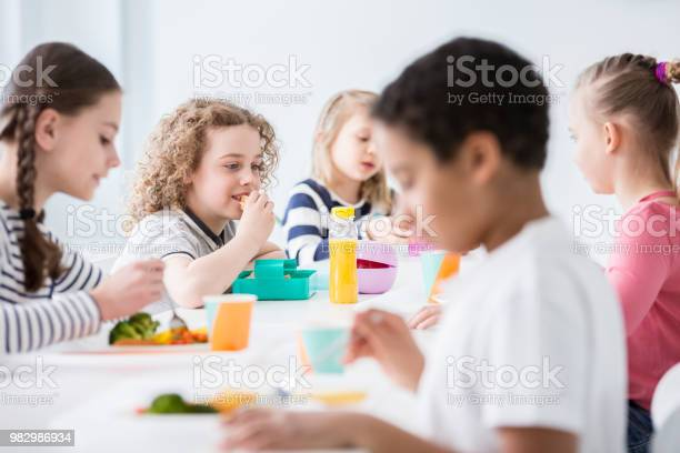 Group of children eating vegetables in the dining hall of school picture id982986934?b=1&k=6&m=982986934&s=612x612&h=0xkjnzniwv078uxi9aa plvfc7rvotbk3545dhg9kd0=