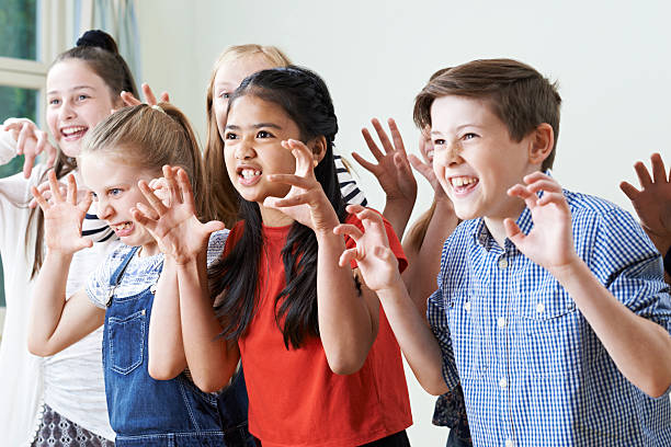 Group Of Children Enjoying Drama Club Together - foto stock