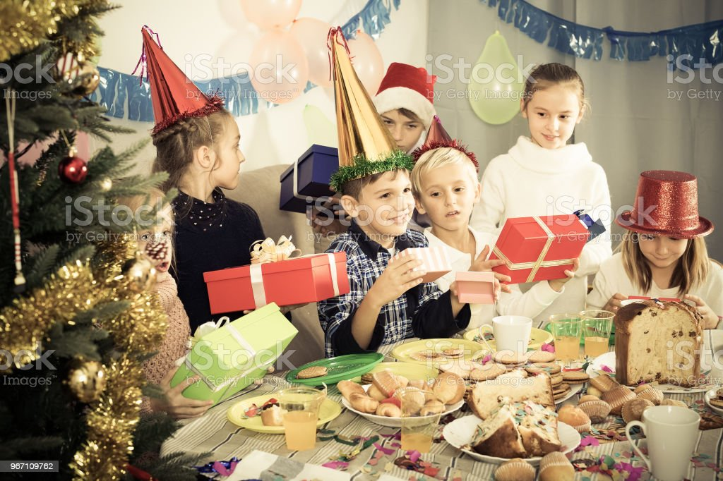 group of children exchanging christmas gifts royalty free stock photo
