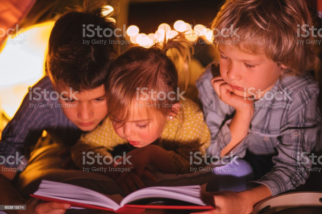 Group of children fascinated by story they are reading stock photo