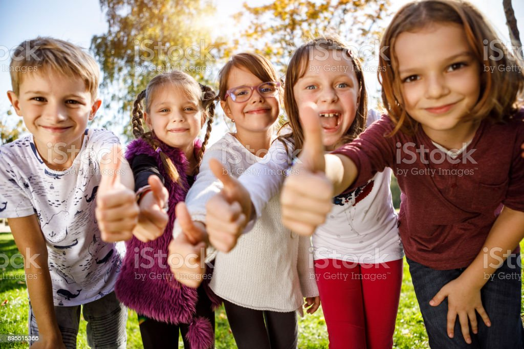 Group of children giving thumbs up stock photo