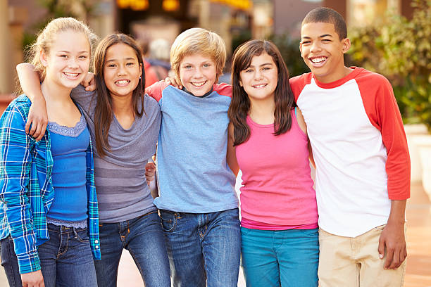 Group Of Children Hanging Out Together In Mall Group Of Children Hanging Out Together In Mall Smiling To Camera 12 13 years stock pictures, royalty-free photos & images