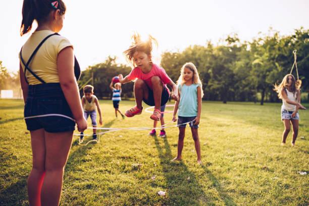 gruppe von kindern hat sportliche aktivität im öffentlichen park - springseil stock-fotos und bilder