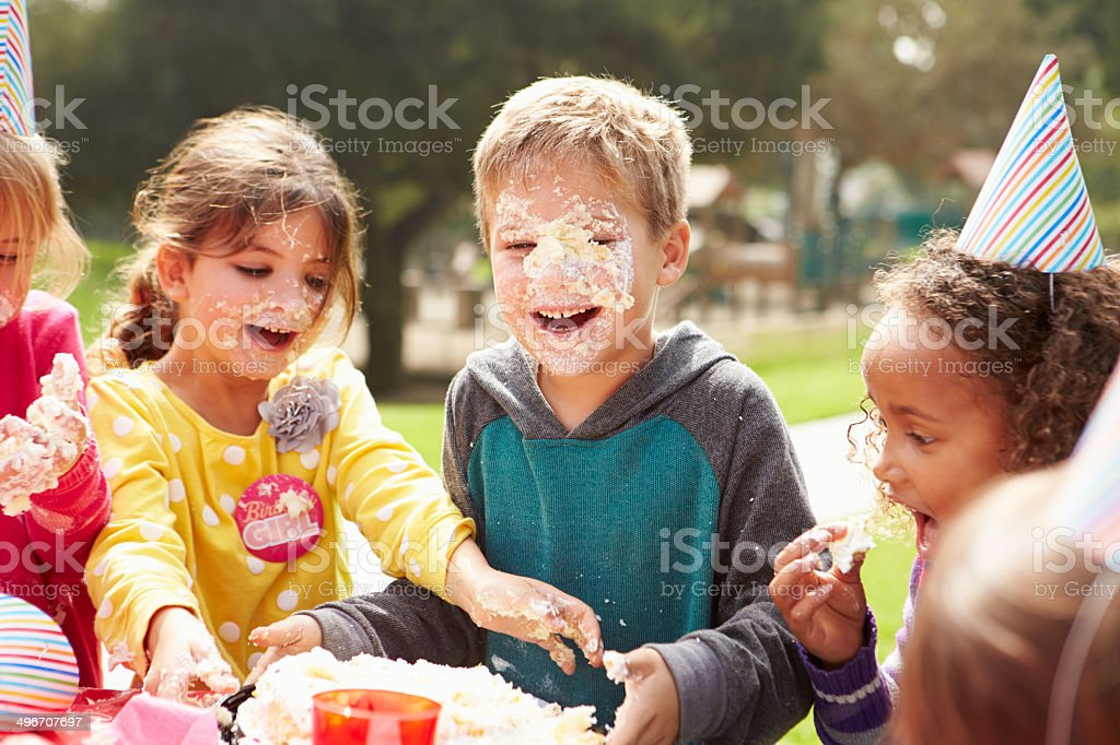 Group Of Children Having Outdoor Birthday Party Group Of Children Having Outdoor Birthday Party With Bithday Cake On Faces 4-5 Years Stock Photo