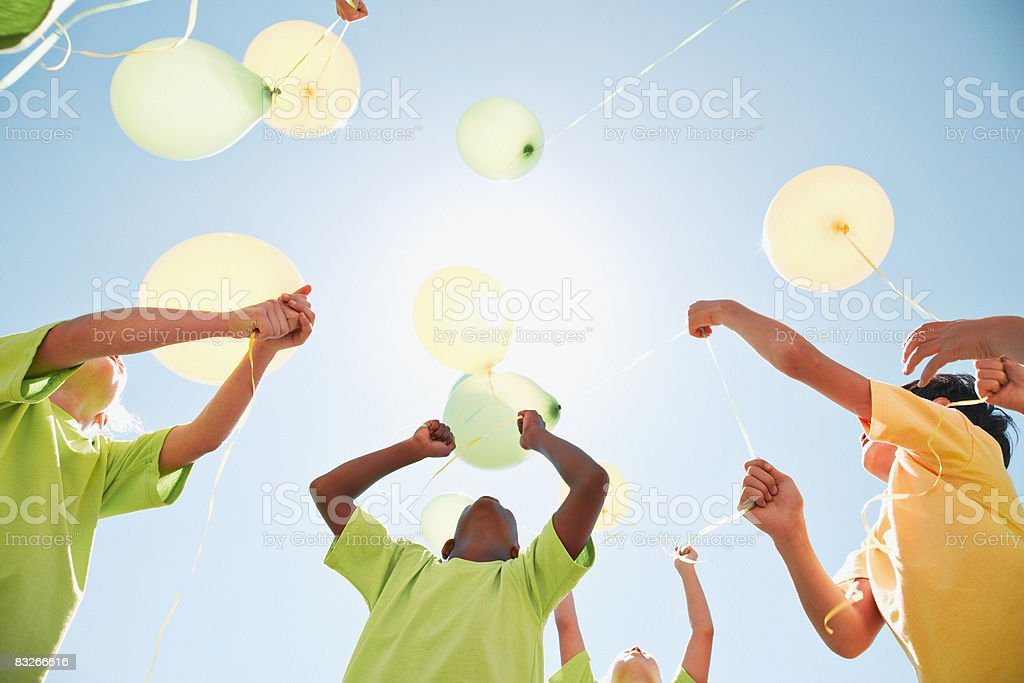 Group of children holding balloons outdoors stock photo