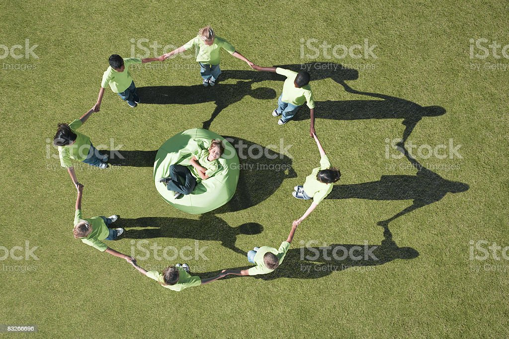 Group of children holding hands around boy in bean bag royalty-free stock photo