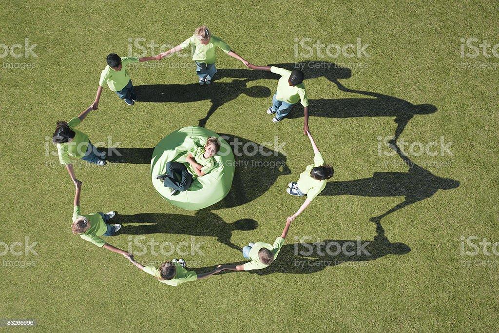 Gruppo di bambini tenendo le mani intorno al bambino in Cuscinone foto stock royalty-free