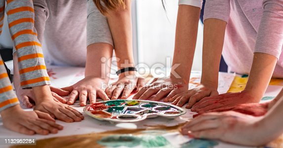 154371635 istock photo Group of children holding hands at the table after drawing 1132952284