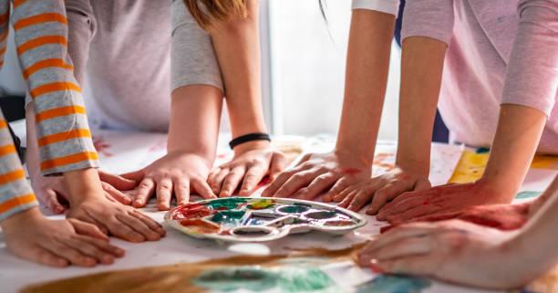 gruppe von kindern, die nach dem zeichnen die hände am tisch halten - naive malerei stock-fotos und bilder