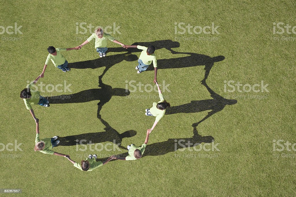 Group of children holding hands in a circle stock photo