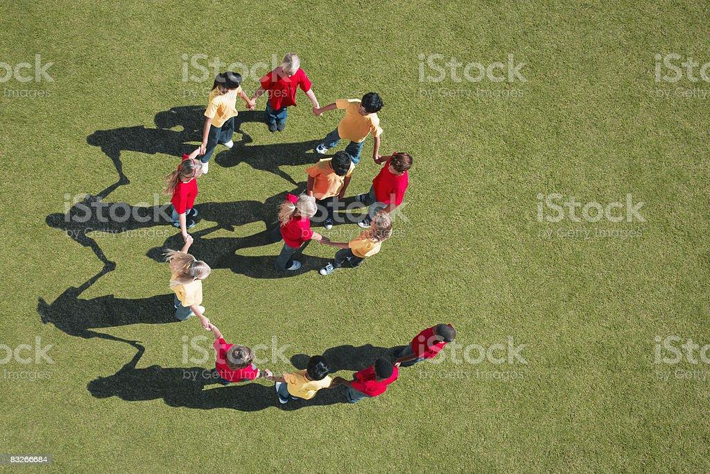Group of children holding hands in spiral formation royaltyfri bildbanksbilder