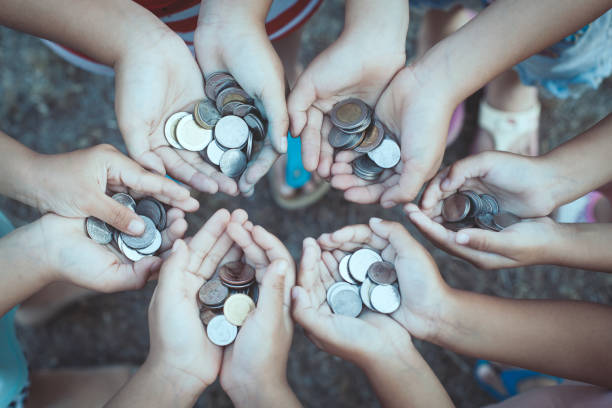 Group of children holding money in hands in the circle together stock photo