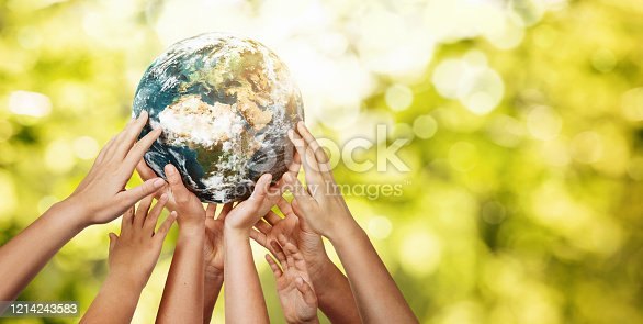 istock Group of children holding planet earth over defocused nature background 1214243583