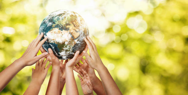Group of children holding planet earth over defocused nature background stock photo