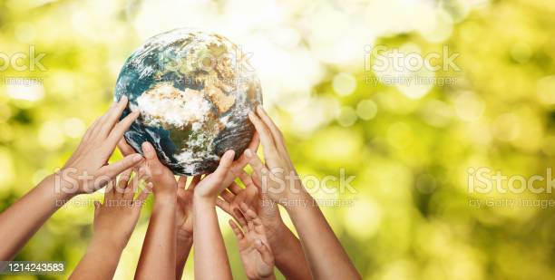 Photo of Group of children holding planet earth over defocused nature background