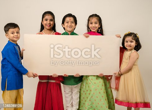 Group of children in tradional clothes holding white board in studio