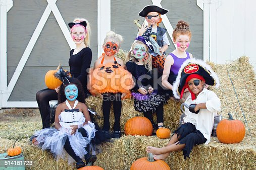 Seven children sitting on bales of straws at a Halloween party and smiling for the camera.