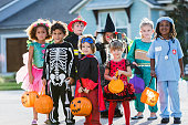 Multi-ethnic group of children 3-6 years old, wearing halloween costumes, ready to go trick or treating, standing in street in front of house.