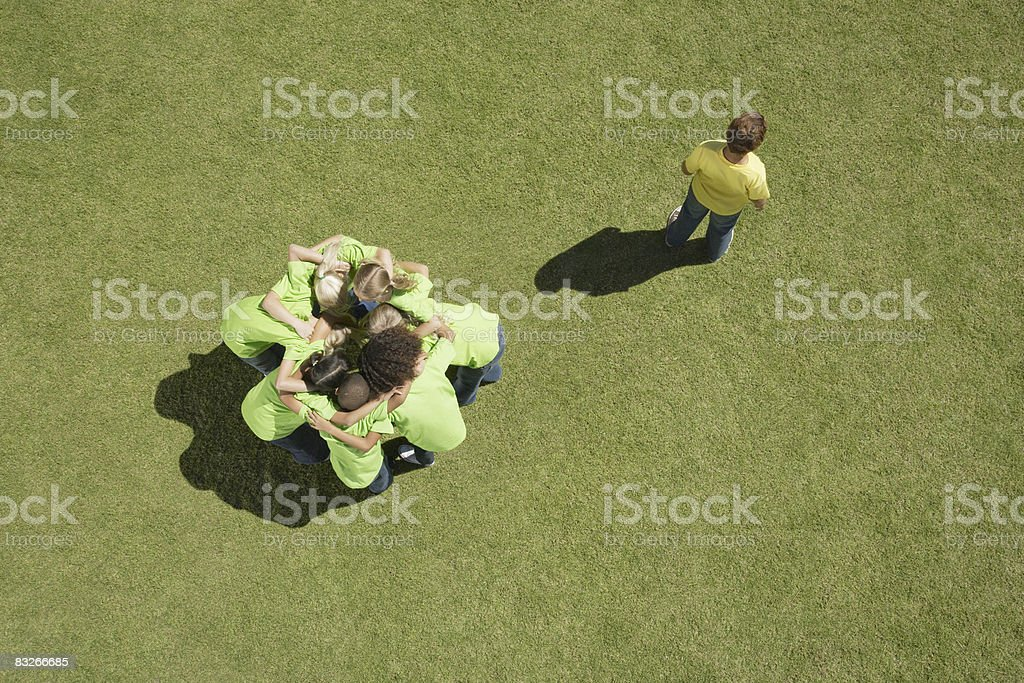 Group of children in huddle with one boy excluded stock photo