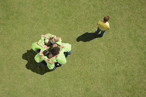 group of children in huddle with one boy excluded - disbarment stock pictures, royalty-free photos & images