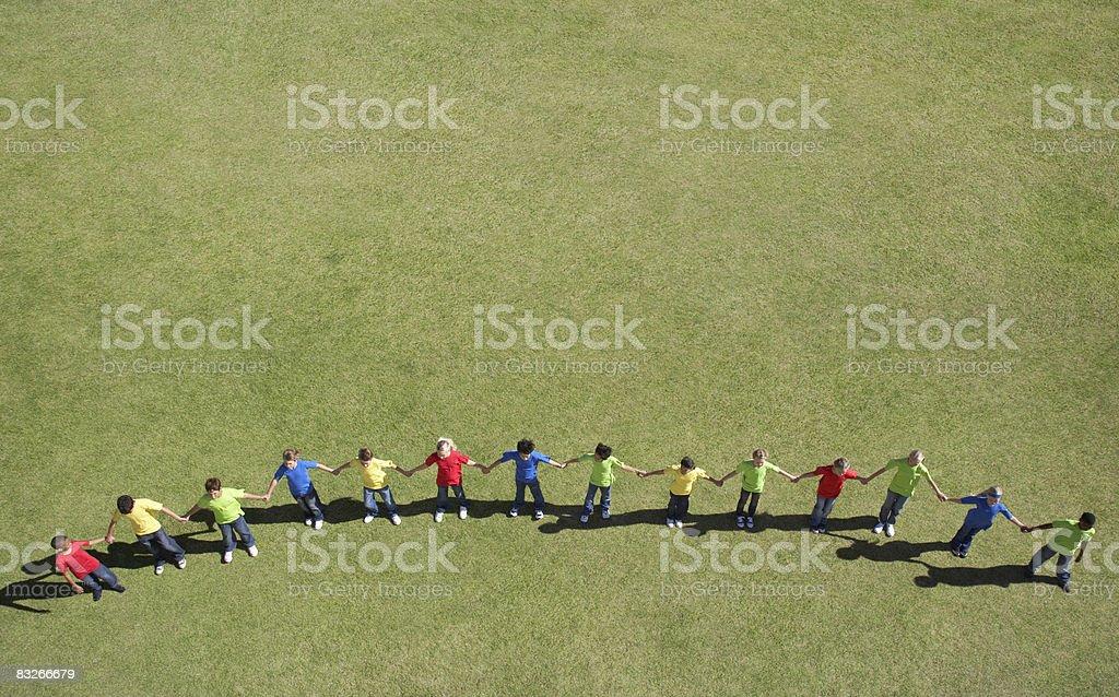 Group of children in line holding hands royaltyfri bildbanksbilder