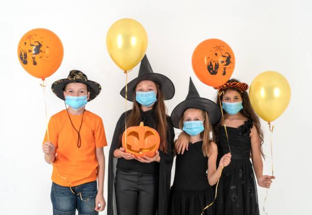 un grupo de niños con máscaras médicas y disfraces de halloween. el concepto de halloween y la pandemia de 2020. - halloween covid fotografías e imágenes de stock