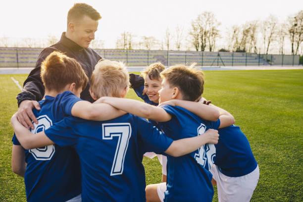 groep van kinderen in het voetbal team vieren met coach - samen sporten stockfoto's en -beelden