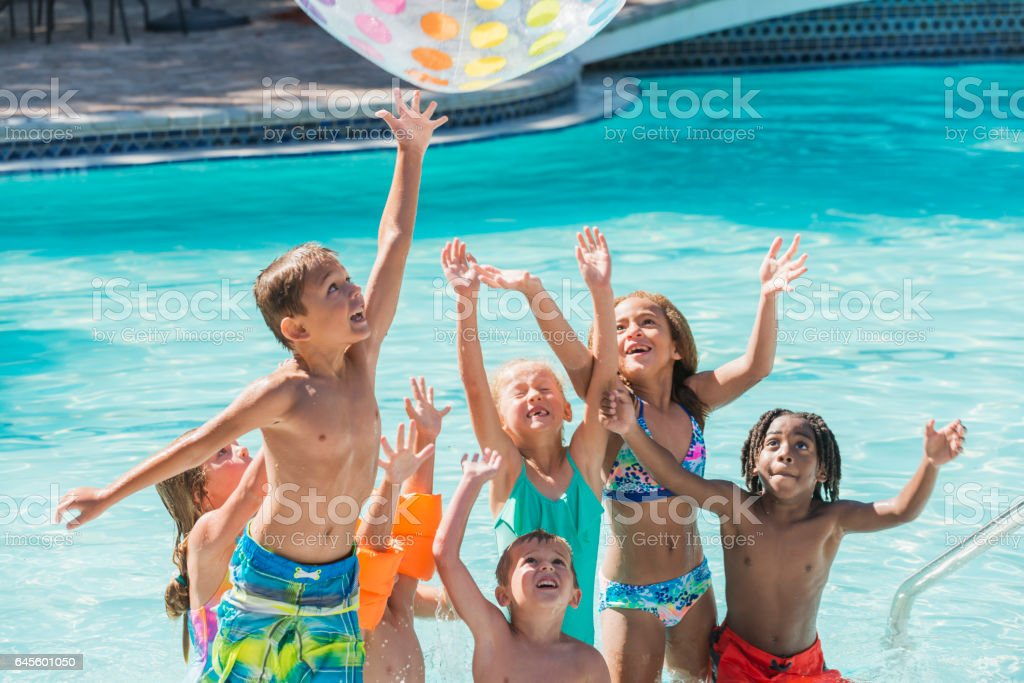 Groupe d'enfants dans la piscine pour atteindre pour la boule - Photo