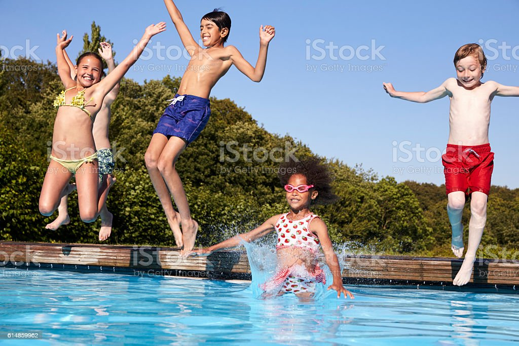 Group Of Children Jumping Into Outdoor Swimming Pool stock photo