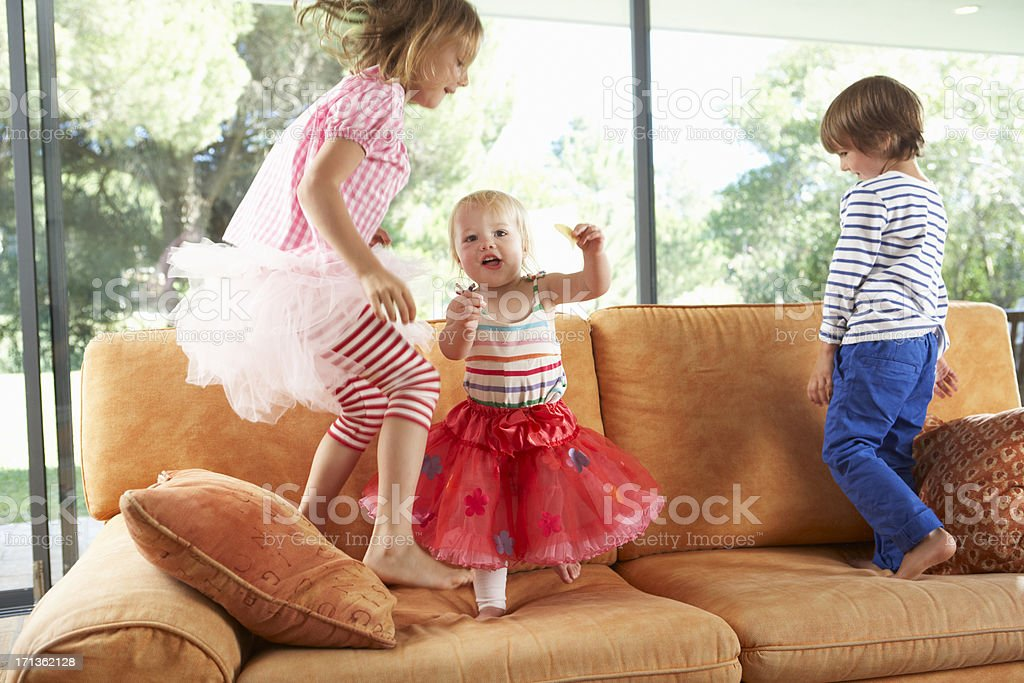 Group Of Children Jumping On Sofa stock photo