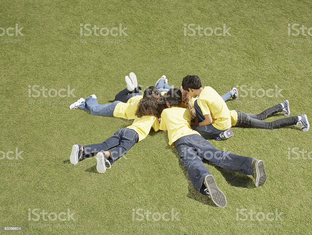 Group of children laying in grass in circle formation royalty-free stock photo