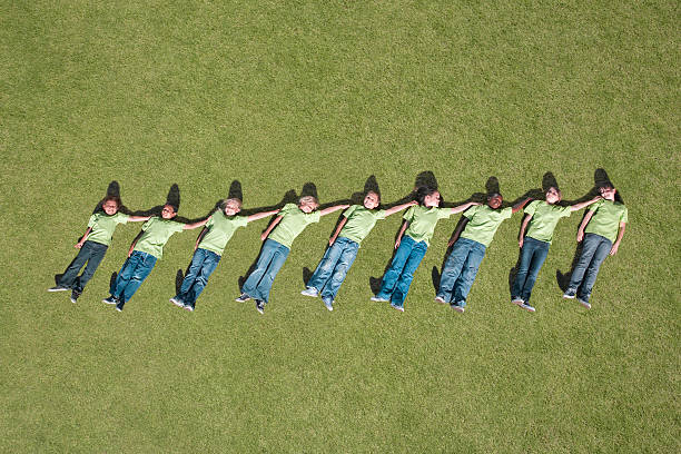 Group of children laying in grass in height ascending order stock photo