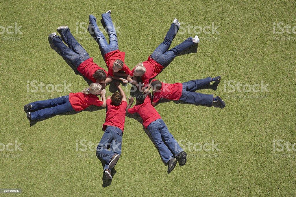 Gruppo di bambini posa sull'erba in un cerchio formazione foto stock royalty-free